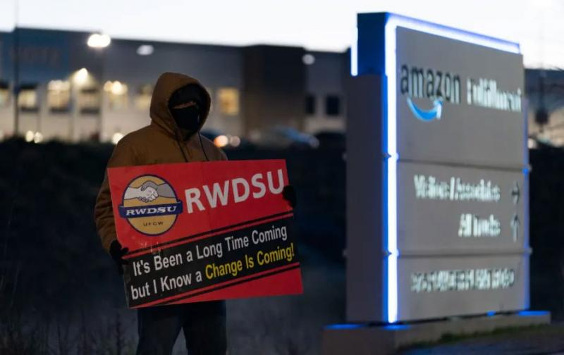 person with pro-union sign standing outside of an Amazon warehouse