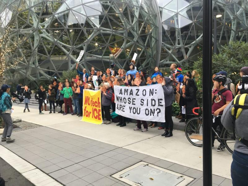 Image of people demonstrating in front of Amazon with signs that say No Tech for Ice and Amazon: Whose Side Are You On?